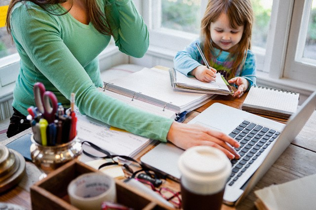 Mother and daughter (4-5) in home office